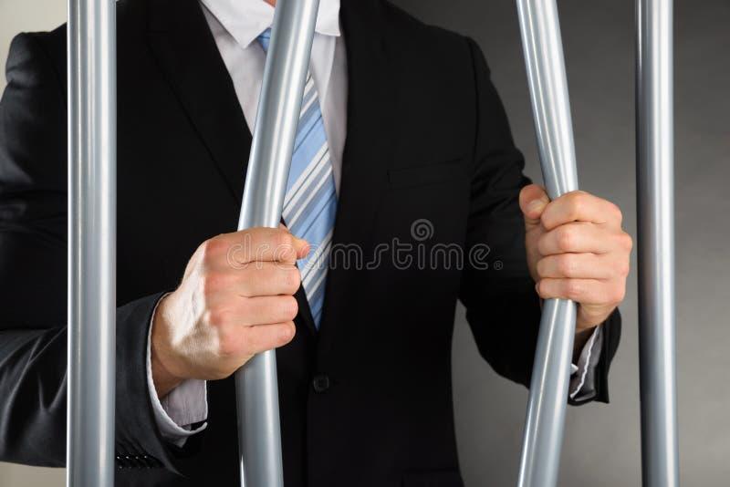 De Gevangenis van zakenmanbending bars of stock afbeeldingen