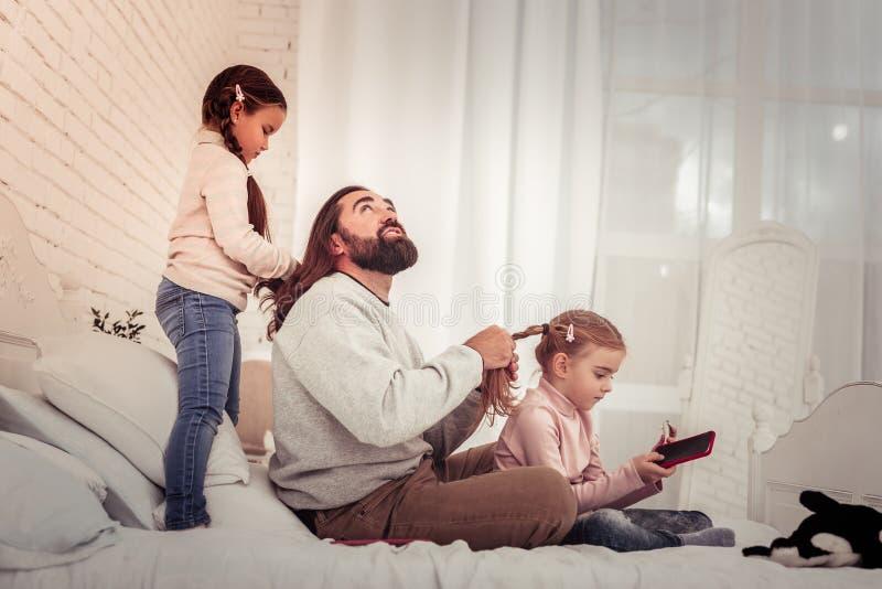 De gevende vader die van Nice een kapsel voor zijn dochter doen royalty-vrije stock afbeeldingen