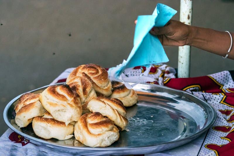 De gevlechte zoete broodjes op een dienblad in openlucht in het stadscentrum van Bemoeiziek zijn, Madagascar stock foto