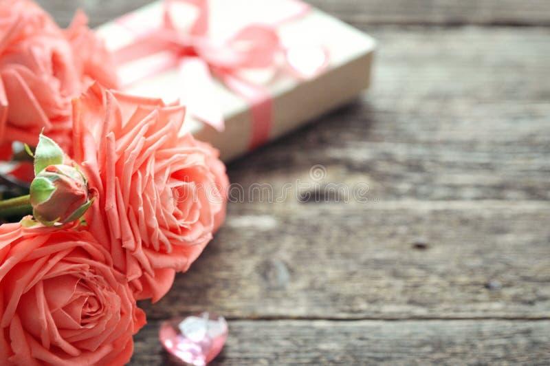 De gevoelig roze rozen en de gift van de koraalschaduw met hart en briefhoofd op rustieke houten achtergrond De achtergrond van d royalty-vrije stock afbeelding