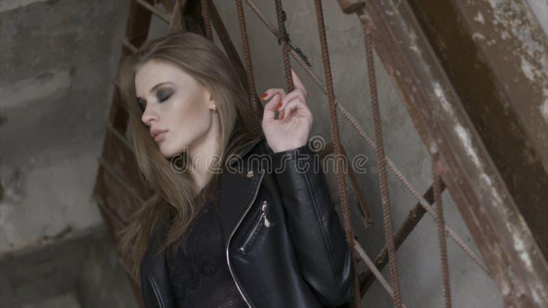 De gevoelige jonge meisje status dichtbij roestig traliewerk wat betreft haar recht bruin haar, straat kijkt concept actie Een mo stock afbeelding