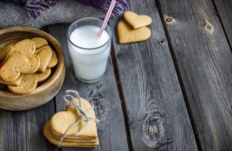 De gevormd koekjes van de valentijnskaartendag hart en glas melk stock foto