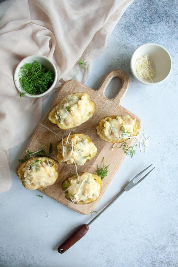 De gevulde aardappelhelften met kip, groenten in het zuur en kaas stock afbeelding