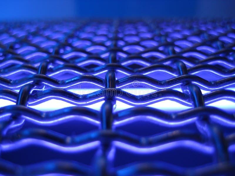 De geweven textuur van het metaalnetwerk met elektrisch blauw licht royalty-vrije stock foto's