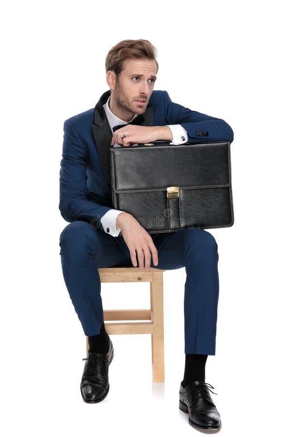 De gezette modieuze mens rust zijn hand op zwarte koffer stock afbeelding