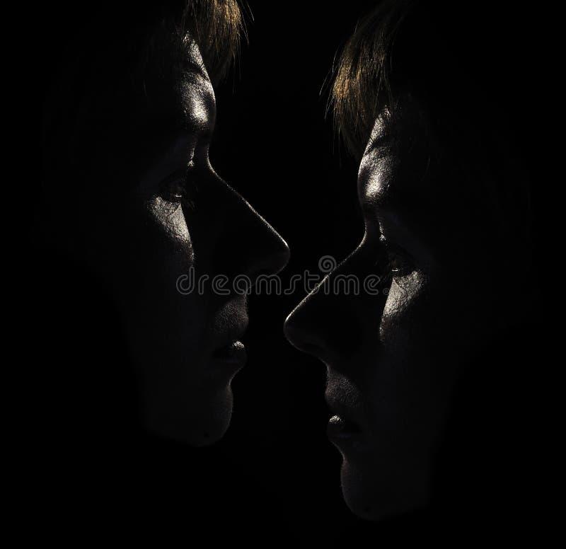 De Gezichten van twee Vrouwen in Dark stock foto