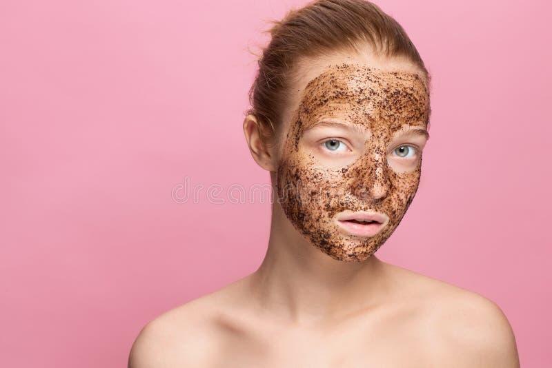 De gezichtshuid schrobt Het portret van Sexy het Glimlachen Vrouwelijk Modelapplying natural coffee Masker, Gezicht schrobt op Ge royalty-vrije stock afbeeldingen