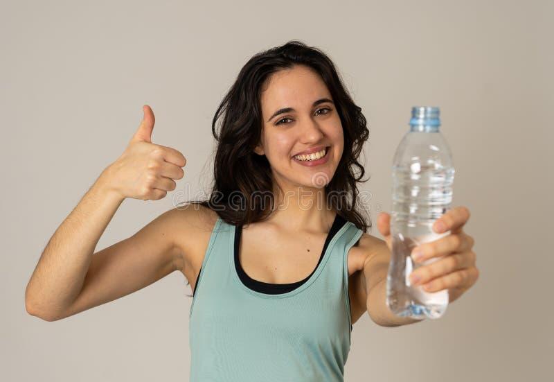 De gezonde aantrekkelijke holding van de sportvrouw en drinkwaterfles in gezond levensstijlconcept stock afbeelding