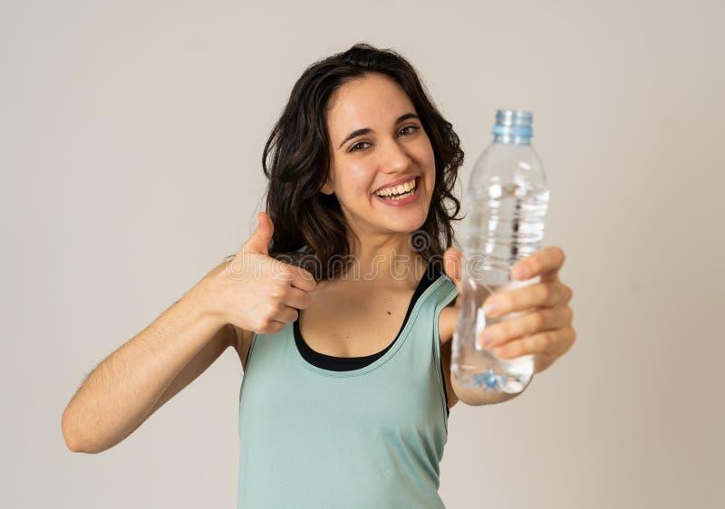 De gezonde aantrekkelijke holding van de sportvrouw en drinkwaterfles in gezond levensstijlconcept royalty-vrije stock foto's