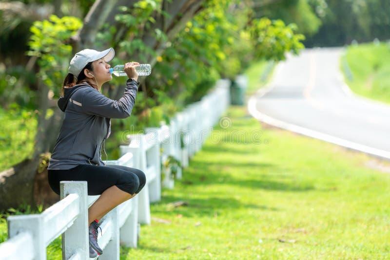 De gezonde atletische Aziatische vrouw drinkt zuiver water van de fles die verfrissen na oefening in het aardpark stock fotografie