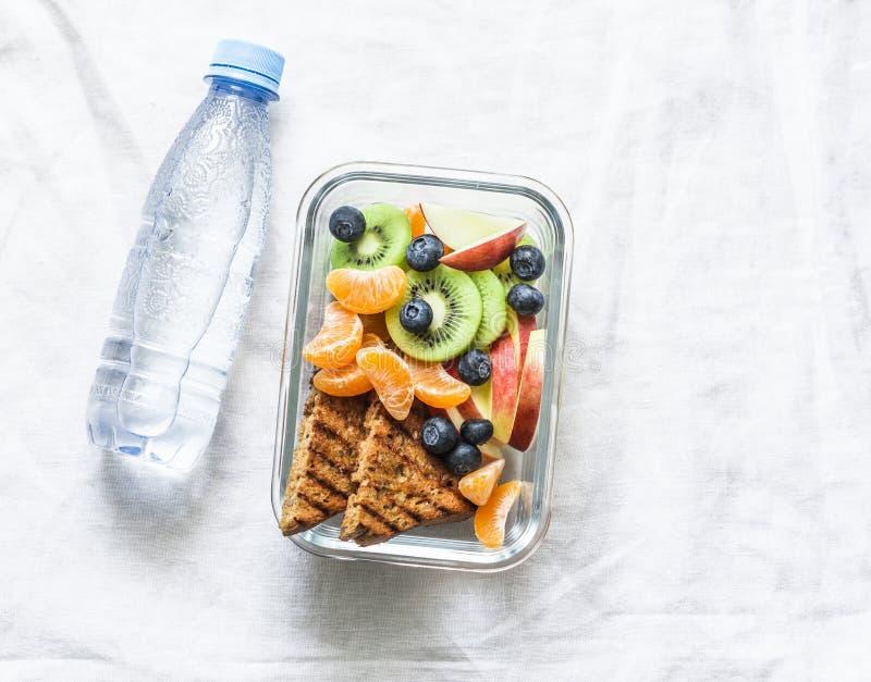 De gezonde doos van de de vitaminelunch van de voedselsnack zoete en fles schoon water op een lichte achtergrond Pindakaastoost,  stock fotografie
