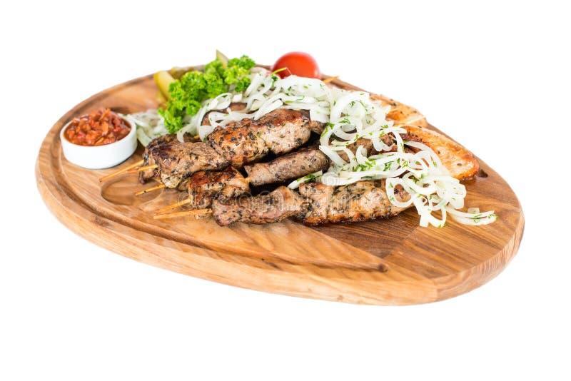 De gezonde geroosterde magere gekubeerde varkensvleeskebabs dienden met een graantortilla en een verse sla en tomatensalade royalty-vrije stock afbeelding