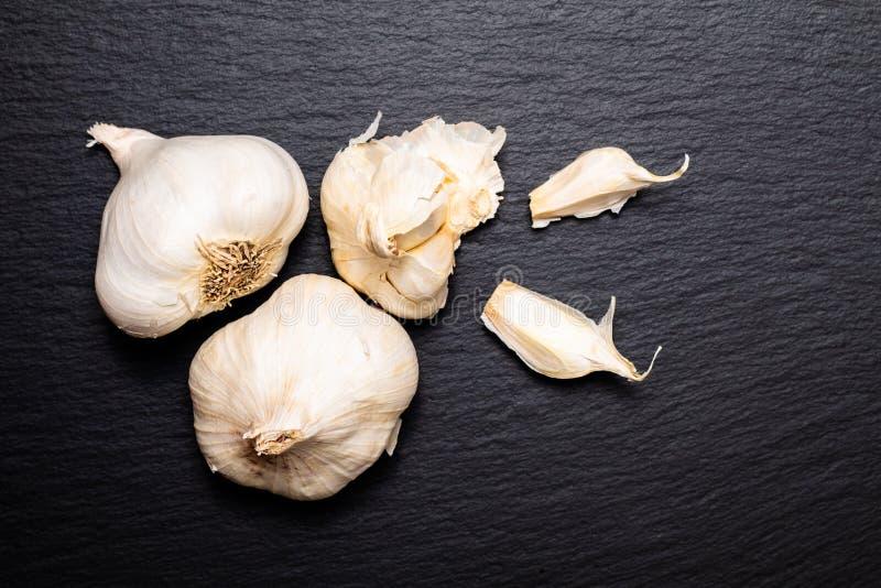 De gezonde Hoogste mening organische Garlics van het Voedselconcept over zwarte leisto royalty-vrije stock foto's