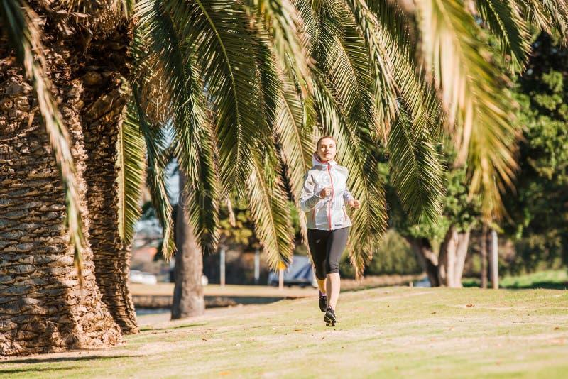 De gezonde jogging van de levensstijl jonge sportieve vrouw bij stock afbeeldingen
