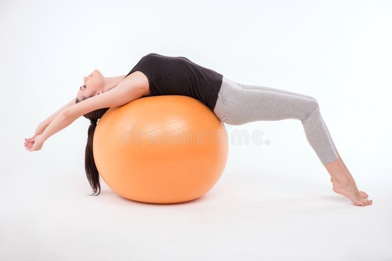 De gezonde jonge sportvrouw doet de oefeningen stock afbeelding