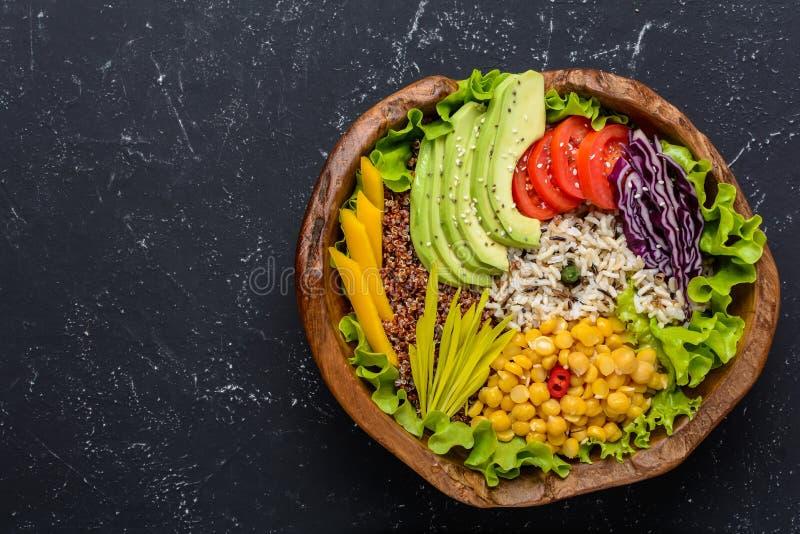 De gezonde kom van het veganistvoedsel met quinoa, wilde rijst, kikkererwt, tomaten, avocado, greens, kool, sla op zwarte steenac royalty-vrije stock foto