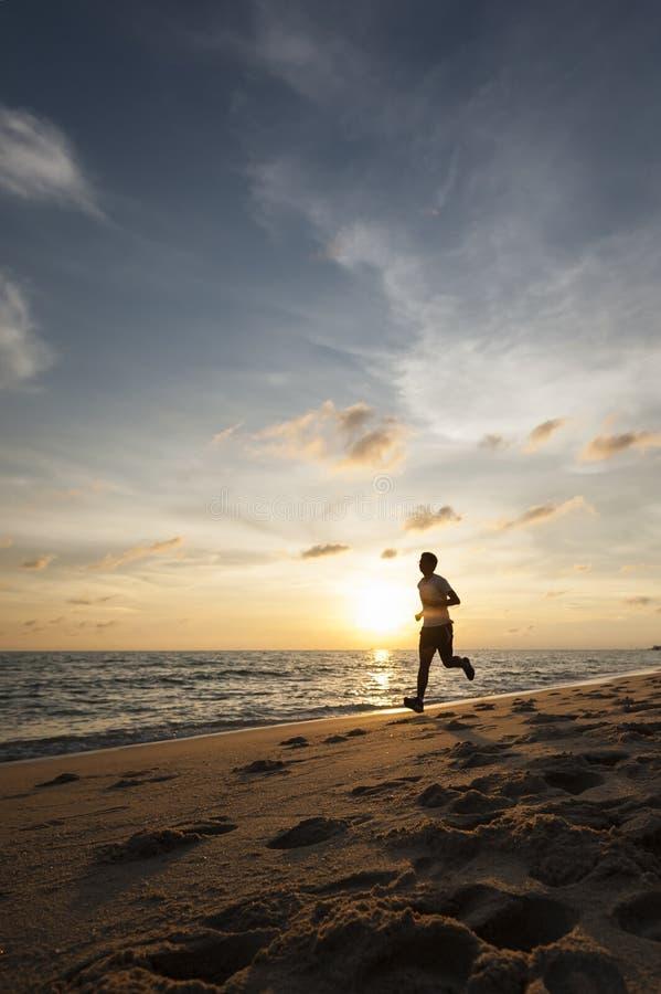 De gezonde lopende agentmens tijdens zonsondergang op de strandtraining stoot aan sunflare door de mist geeft atmosferisch voelen stock afbeelding