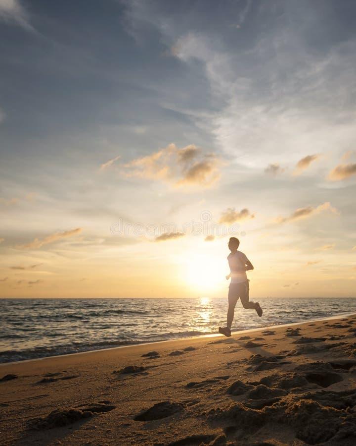De gezonde lopende agentmens tijdens zonsondergang op de strandtraining stoot aan sunflare door de mist geeft atmosferisch voelen royalty-vrije stock foto's