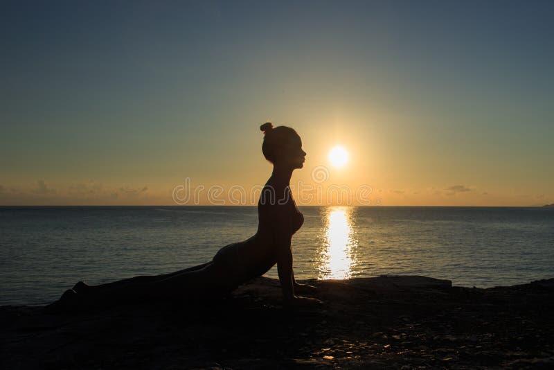 De gezonde meditatie van de yogavrouw bij zonsopgangkust royalty-vrije stock fotografie