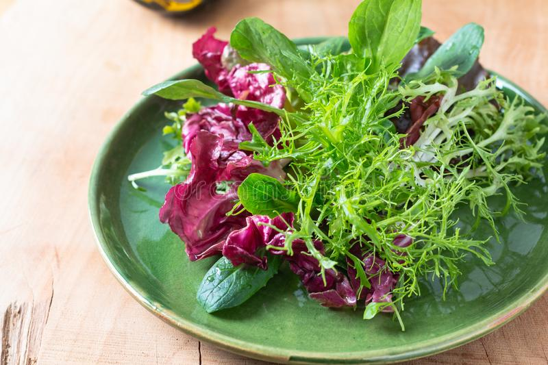De gezonde Mengeling van het voedselconcept van groentensalade in groene plaat op houten achtergrond met exemplaarruimte stock foto's