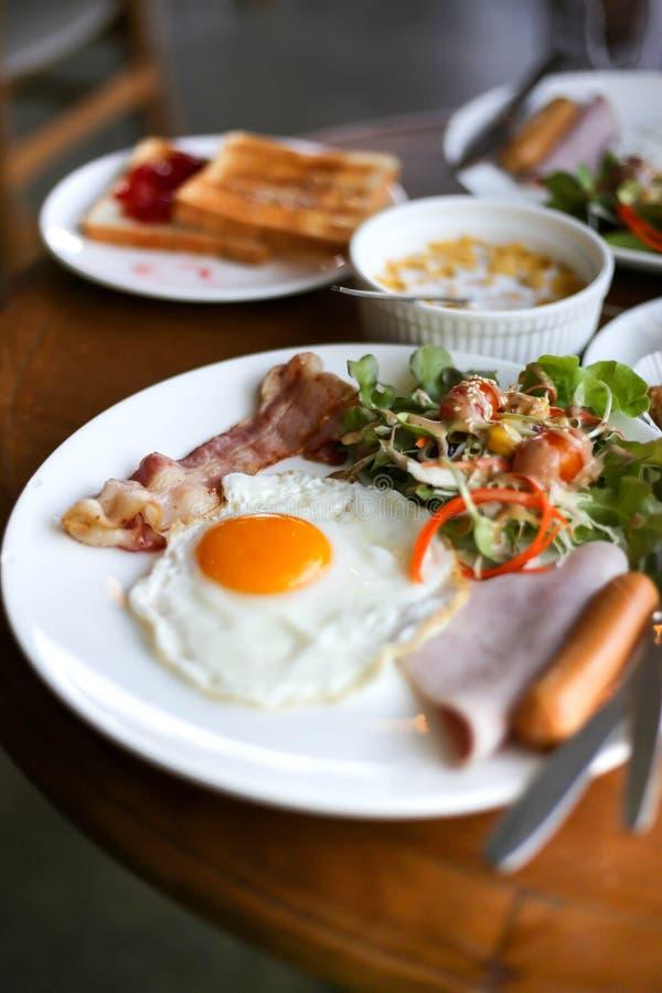 De gezonde ontbijtverspreiding op een lijst met koffie, jus d'orange, fruit, muesli, rookte zalm, ei, croissants, vlees en kaas royalty-vrije stock foto