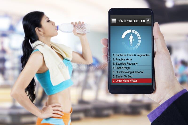 De gezonde resolutie app en de vrouw drinken water stock foto