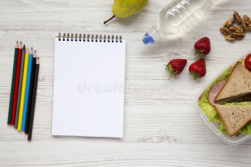 De gezonde schoolmaaltijddoos met notitieboekje en kleurenpotloden op witte houten vlakke achtergrond, legt Van hierboven Hoogste stock foto's
