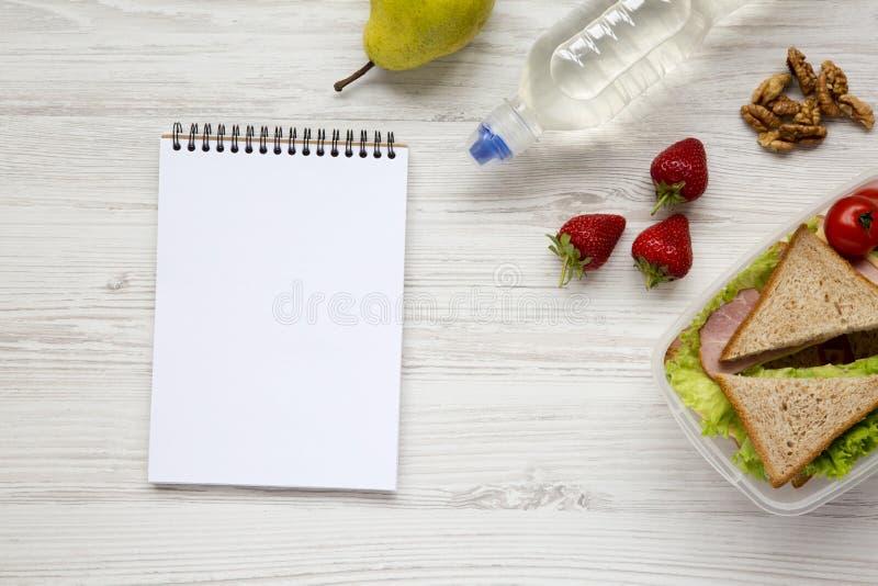 De gezonde schoolmaaltijddoos met notitieboekje op witte houten vlakke achtergrond, legt Van hierboven Hoogste mening stock afbeeldingen