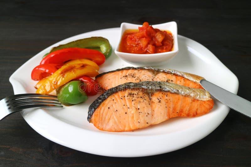 De gezonde schotel van geroosterde zalmlapjes vlees met kleurrijke groenten diende op donkere bruine houten lijst stock afbeelding