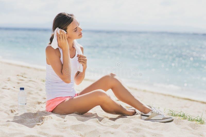 De gezonde sportieve vrouw doet haar zweet met handdoek na training teniet stock afbeelding