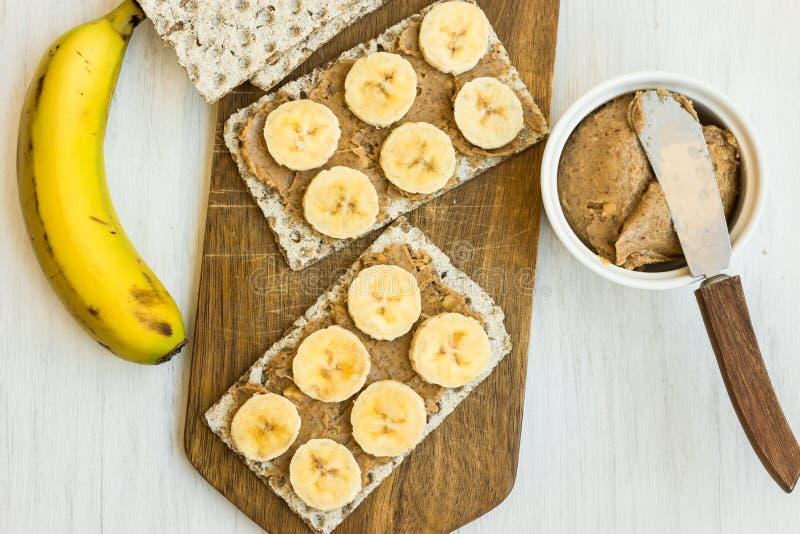 De gezonde veganist eigengemaakte ruige pindakaas en de banaan klemmen met Zweeds geheel korrelknäckebrood op houten scherpe raad stock fotografie
