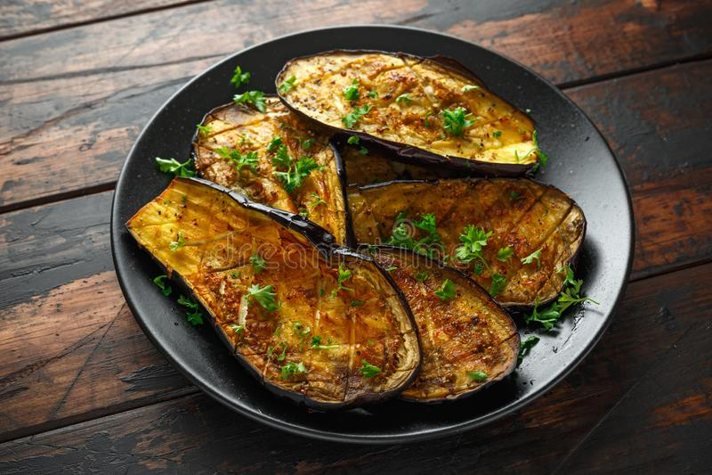 De gezonde vegeterainoven bakte aubergines, Aubergine met peterselie en kruiden in een zwarte plaat stock afbeeldingen