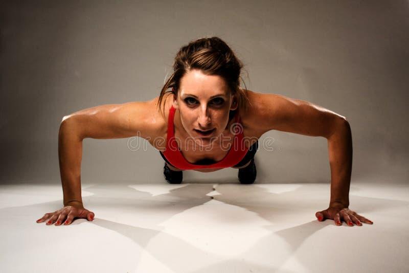 De gezonde Vrouw die van de Geschiktheid een Opdrukoefening doet stock afbeeldingen