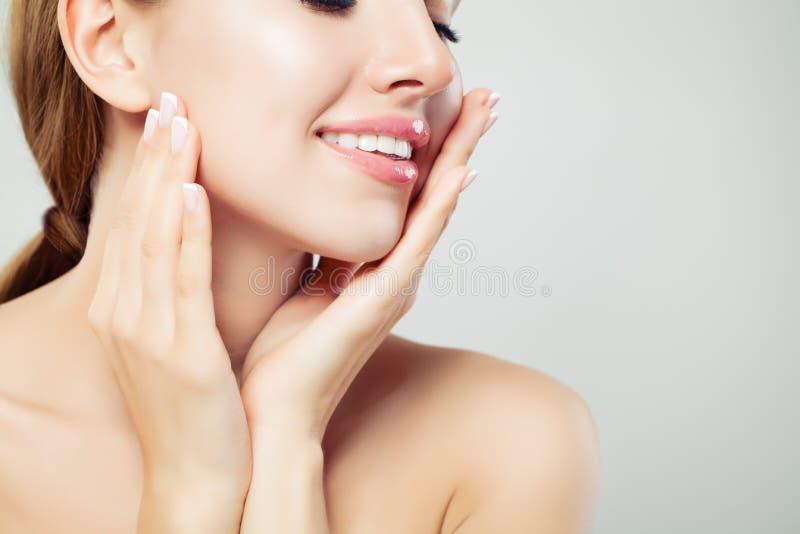 De gezonde vrouwenlippen met glanzende roze make-up en manicured handen met Franse manicurespijkers, gezichtsclose-up royalty-vrije stock afbeelding