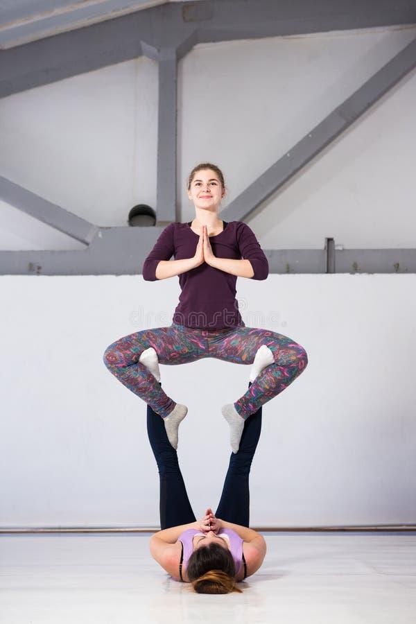De gezondheids acrobatische yoga van themasporten Een paar van twee jonge Kaukasische meisjes in de gymnastiek die een basis van  royalty-vrije stock foto's