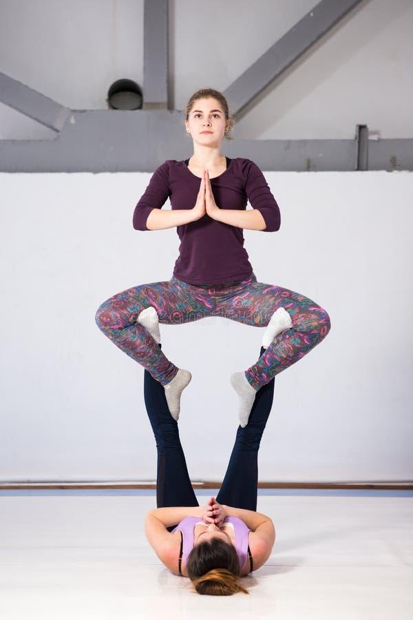 De gezondheids acrobatische yoga van themasporten Een paar van twee jonge Kaukasische meisjes in de gymnastiek die een basis van  royalty-vrije stock afbeeldingen