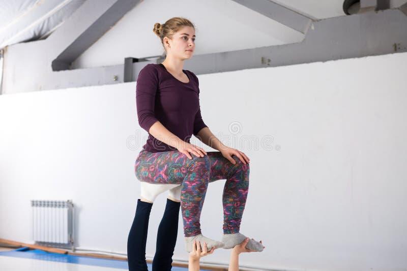 De gezondheids acrobatische yoga van themasporten Een paar van twee jonge Kaukasische meisjes in de gymnastiek die een stoel van  royalty-vrije stock foto's