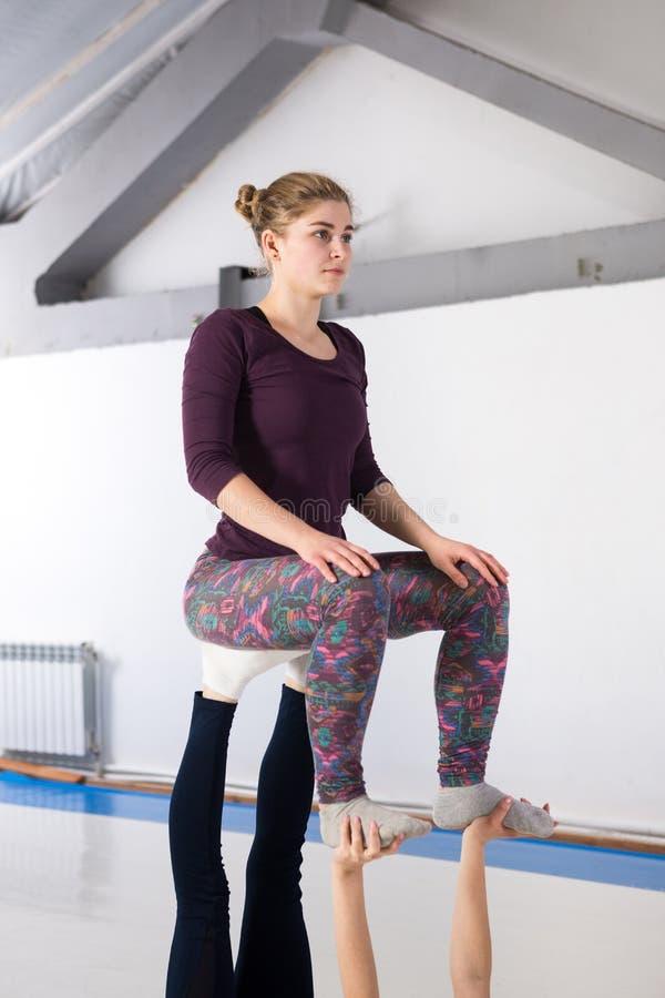 De gezondheids acrobatische yoga van themasporten Een paar van twee jonge Kaukasische meisjes in de gymnastiek die een stoel van  stock afbeeldingen
