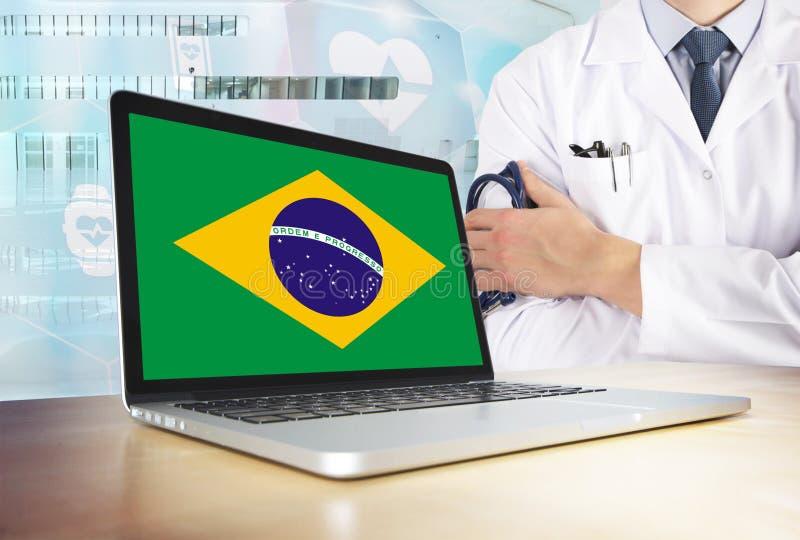 De gezondheidszorgsysteem van Brazilië in technologie-thema Braziliaanse vlag op het computerscherm Arts die zich met stethoscoop stock afbeelding
