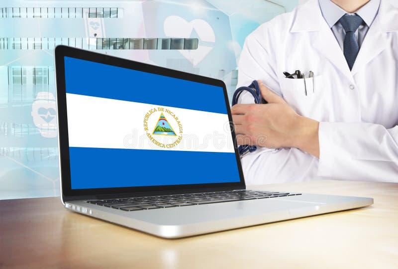 De gezondheidszorgsysteem van Nicaragua in technologie-thema Nicaraguan vlag op het computerscherm Arts die zich met stethoscoop  stock afbeelding
