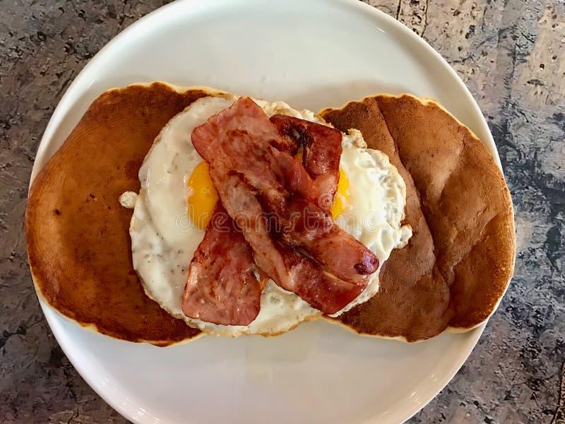 De gezouten Pannekoek met Eieren en het Knapperige Bacon voor Zout Ontbijt dienden met Koffie stock foto