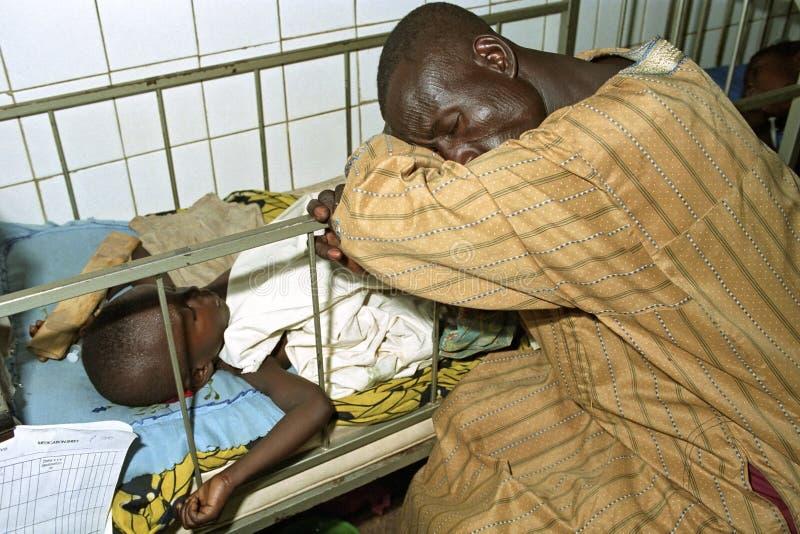 De Ghanese vader bewaakt zijn ziek kind in het ziekenhuis royalty-vrije stock fotografie