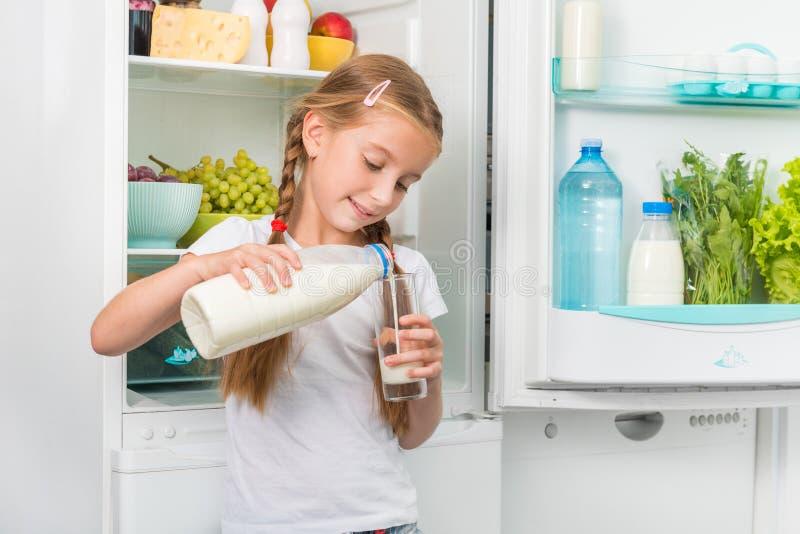 De gietende melk van het meisje in glas stock foto's