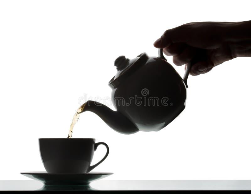 De gietende thee van de theepot in een kop stock foto