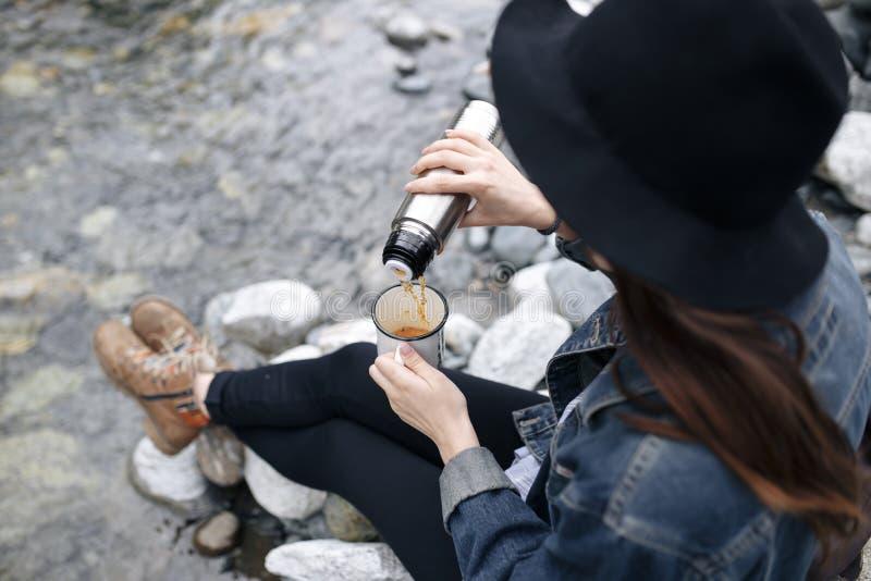 De gietende thee van het reizigersmeisje van thermosflessenkop, in openlucht Jonge vrouw het drinken thee bij kop Themareis Vrouw stock foto