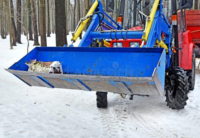 De gietlepel van de tractorlader in hout in de winter royalty-vrije stock foto's