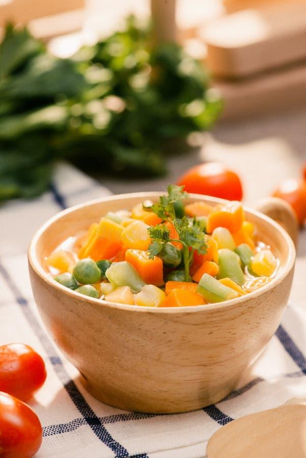 De gietlepel van gestoomde vers geoogste jonge groenten met inbegrip van kreukbesnoeiing sneed wortelen, erwten en aardappel voor stock foto