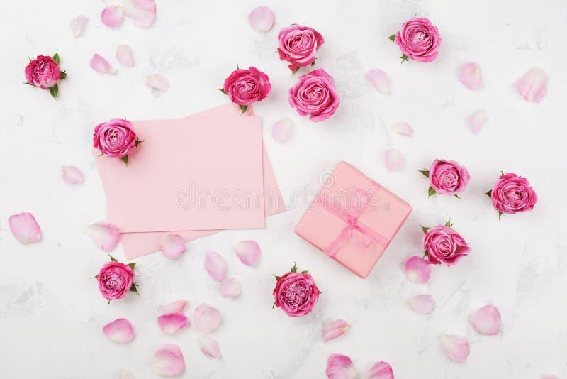 De gift of het huidige vakje, envelop, document spatie, bloemblaadjes en roze nam bloem op de witte mening van de lijstbovenkant  stock fotografie