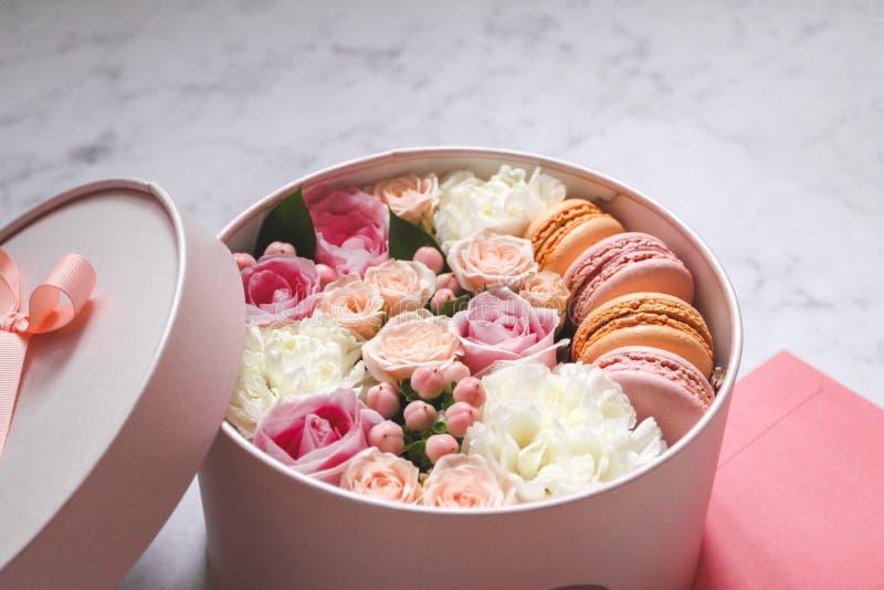 De gift om vakje met bloemen, rozen en makaronsamandel koekt met roze envelop op de lijst stock foto's