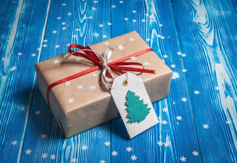 De gift van close-upkerstmis met een rood lint op een blauwe achtergrond met sneeuwvlokken stock afbeeldingen
